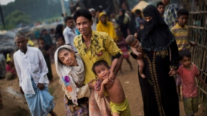 In this Sept. 5, 2017, file photo, an exhausted Rohingya helps an elderly family member and a child as they arrive at Kutupalong refugee camp after crossing from Myanmmar to the Bangladesh side of the border, in Ukhia. (Bernat Armangue/AP Photo)