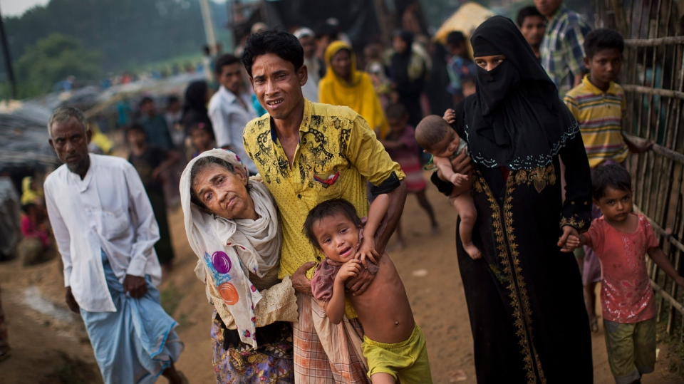 An exhausted Rohingya helps an elderly family member and a child as they arrive at Kutupalong refugee camp after crossing from Myanmmar to the Bangladesh side of the border, in Ukhia on Sept. 5, 2017. (AP Photo/Bernat Armangue)