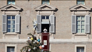 Framed by a Christmas tree, Pope Francis delivers his speech during the Angelus noon prayer from his studio window overlooking St. Peter's Square at the Vatican, Sunday, Dec. 24, 2017. (AP Photo/Alessandra Tarantino)