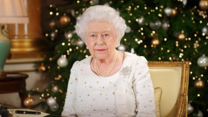 In this photo released on Monday, Dec. 25, 2017, Queen Elizabeth sits at a desk in the 1844 Room at Buckingham Palace, after recording her Christmas Day broadcast to the Commonwealth, in London. (Pool Photo via AP)