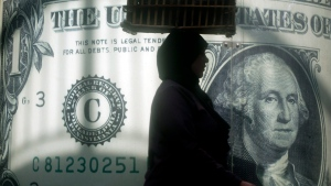 In this Nov. 9, 2016 file photo, an Egyptian vendor walks past a poster depicting a U.S. dollar outside an exchange office in Cairo, Egypt. (AP / Amr Nabil, File)