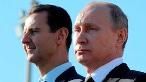 In this Monday, Dec. 11, 2017 file photo, Russian President Vladimir Putin, right, and Syrian President Bashar Assad watch the troops marching at the Hemeimeem air base in Syria. (Mikhail Klimentyev, Sputnik, Kremlin Pool Photo via AP)