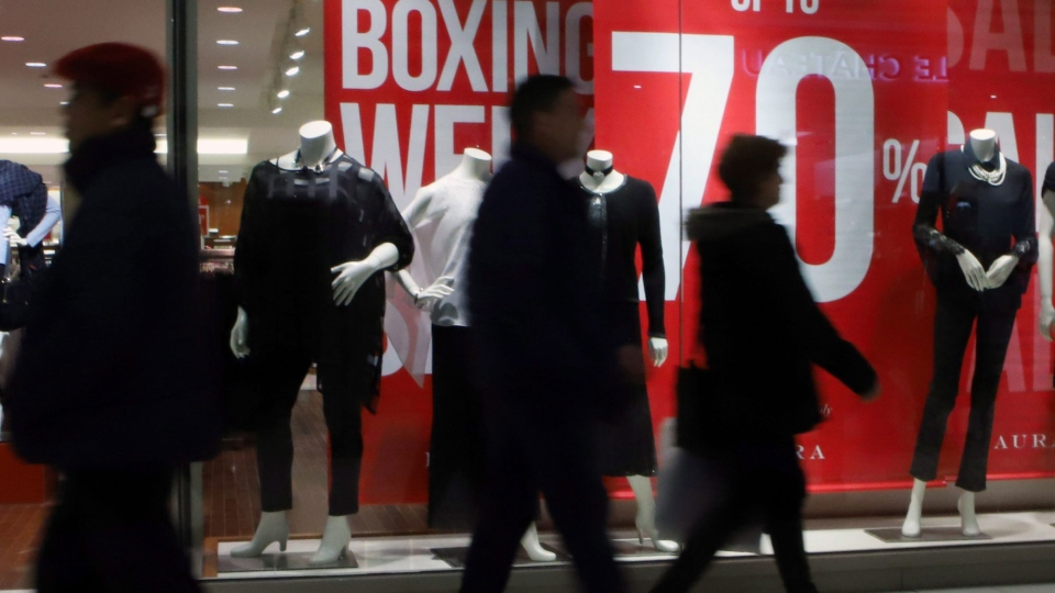 People walk past a clothing store during BoxingDay sales at a mall in Ottawa, Tuesday, December 26, 2017. THE CANADIAN PRESS/Fred Chartrand