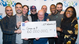 Lotto Max winners Julie Beland, Haidar Abi Haidar, Robert Macri, Diane Dorele Fossouo Djuidje, Nathaniel Thomas, Darius Hozhabr Zandi, Peter Jewett, Randolph Dandan and Enzo Scattone hold up a cheque for $60,000,000 in Montreal, Wednesday, December 27, 2017, after they won the jackpot on Friday, December 22 in Montreal. THE CANADIAN PRESS/Graham Hughes