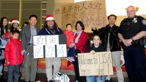 """In this photo taken early morning of Dec 24, 2017 and released by China Aid, Li Aijie, center in red with her son Li Mutian poses for a photo with the airport staff and the staff and family members from China Aid near signs which reads """"The people of Texas welcomes Li Aijie and son, Merry Christmas"""" and """"Freedom Zhang Haitao"""" upon their arrival at the Midland International Airport in Midland, Texas. (China Aid via AP)"""