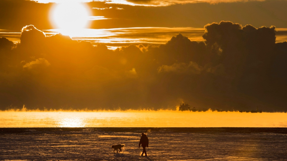 A man walks his dog across the snow covered beach while a cargo ship sits in the steaming fog of Lake Ontario in Toronto on Wednesday December 27, 2017. (THE CANADIAN PRESS/Frank Gunn)