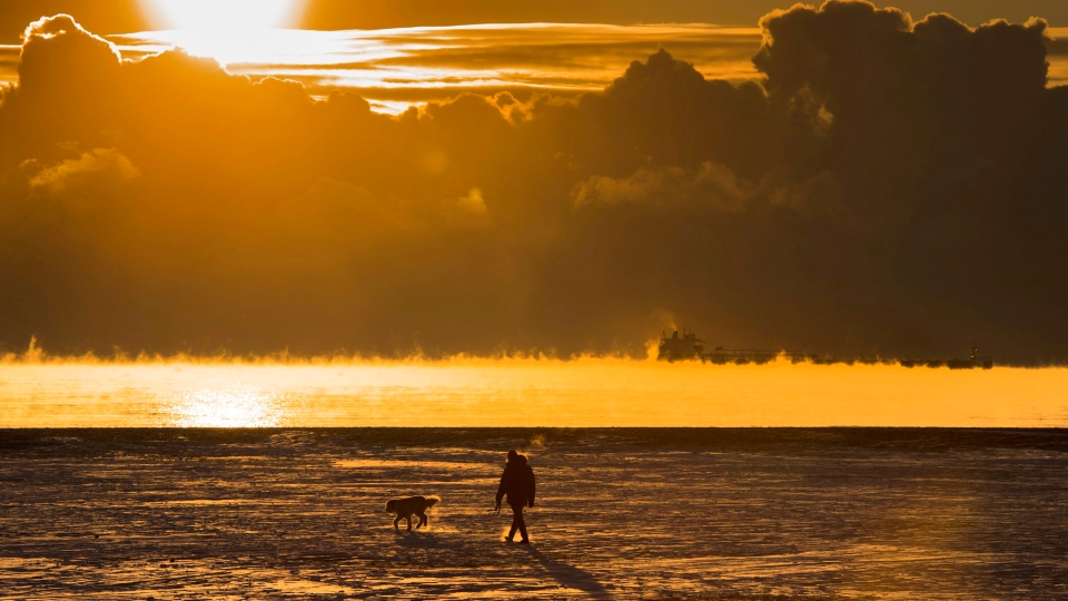 A man walks his dog across the snow-covered beach while a cargo ship sits in the steaming fog of Lake Ontario in Toronto on Dec. 27, 2017. Extreme cold temperatures have covered much of North America. (THE CANADIAN PRESS/Frank Gunn