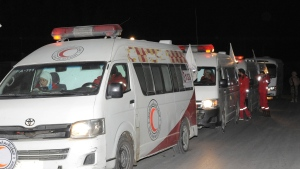 In this photo released by the Syrian official news agency SANA, members of the Syrian Arab Red Crescent gather near their ambulances during a human evacuation of sick and wounded people from the eastern Ghouta, near Damascus, Syria, Thursday, Dec. 28, 2017. (SANA via AP)