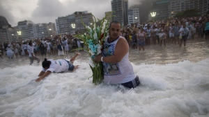 A faithful carries flowers as an offering for Yemanja, goddess of the sea, during a ceremony that is part of traditional New Year's celebrations on Copacabana beach in Rio de Janeiro, Brazil, Friday, Dec. 29, 2017. (AP Photo/Leo Correa)