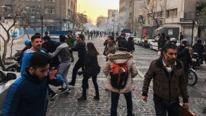 In this photo taken by an individual not employed by the Associated Press and obtained by the AP outside of Iran, people are affected by tear gas fired by anti-riot Iranian police to disperse demonstrators in a protest over Iran's weak economy, in Tehran, Iran, Saturday, Dec. 30, 2017. A wave of spontaneous protests over Iran's weak economy swept into Tehran on Saturday, with college students and others chanting against the government just hours after hard-liners held their own rally in support of the Islamic Republic's clerical establishment. (AP Photo)