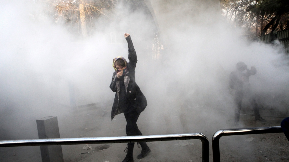 In this photo taken by an individual not employed by the Associated Press and obtained by the AP outside Iran, a university student attends a protest inside Tehran University while a smoke grenade is thrown by anti-riot Iranian police, in Tehran, Iran, Saturday, Dec. 30, 2017. (AP Photo)
