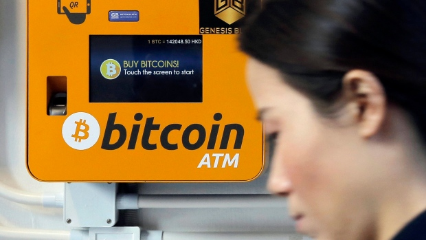 A woman walks past the Bitcoin ATM in Hong Kong.