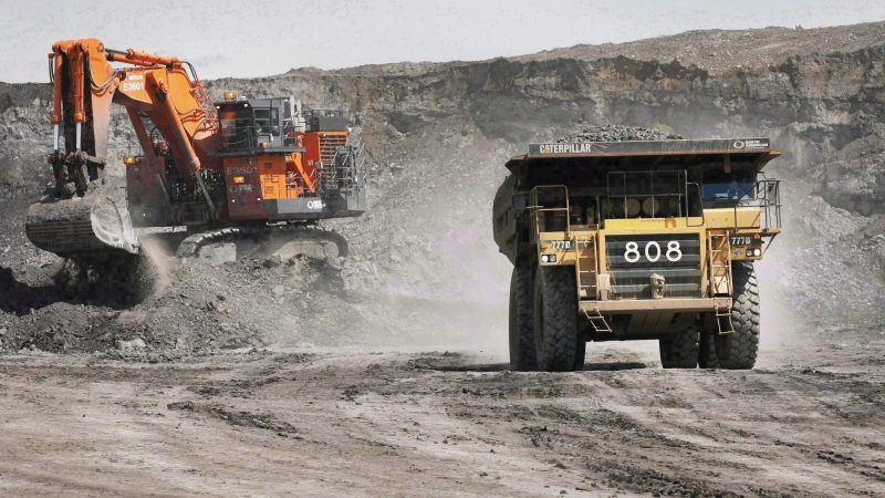 A haul truck carrying a full load drives away from a mining shovel at the Shell Albian Sands oilsands mine near Fort McMurray, Alta., on Monday.July 9, 2008. (THE CANADIAN PRESS/Jeff McIntosh)