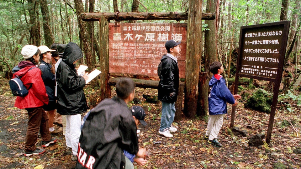 In this Thursday, Oct. 22, 1998, file photo a group of schoolchildren read signs posted in the dense woods of the Aokigahara Forest at the base of Mount Fuji, Japan. (AP Photo/Atsushi Tsukada, File)