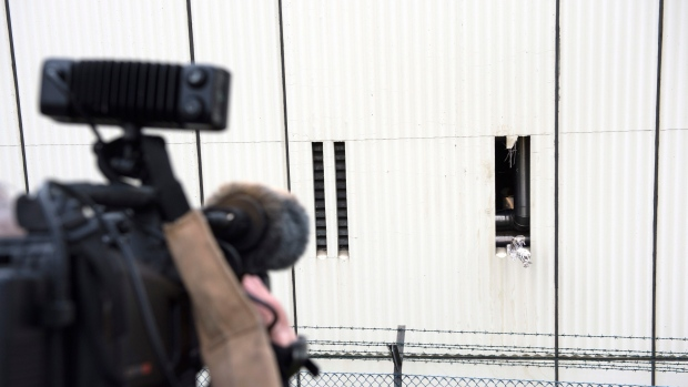 In this Dec. 28, 2017 file photo a cameraman films the broken ventilation slot at the workshop building on the ground of the Ploetzensee prison in Berlin, Germany, where four detainees have escaped from a local prison. (Paul Zinken/dpa via AP, file)