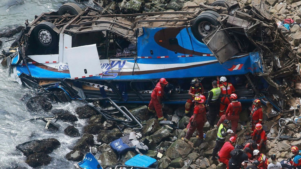 In this photo provided by the government news agency Andina, firemen recover bodies from a bus that fell off a cliff after it was hit by a tractor-trailer rig, in Pasamayo, Peru, Tuesday, Jan 2, 2018. (Vidal Tarky, Andina News Agency via AP)