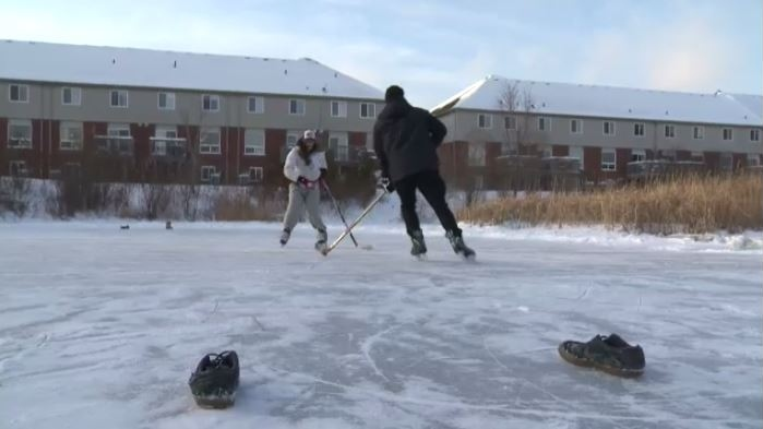 Two people skate on a stormwater management pond off Robert Ferrie Drive in Kitchener.