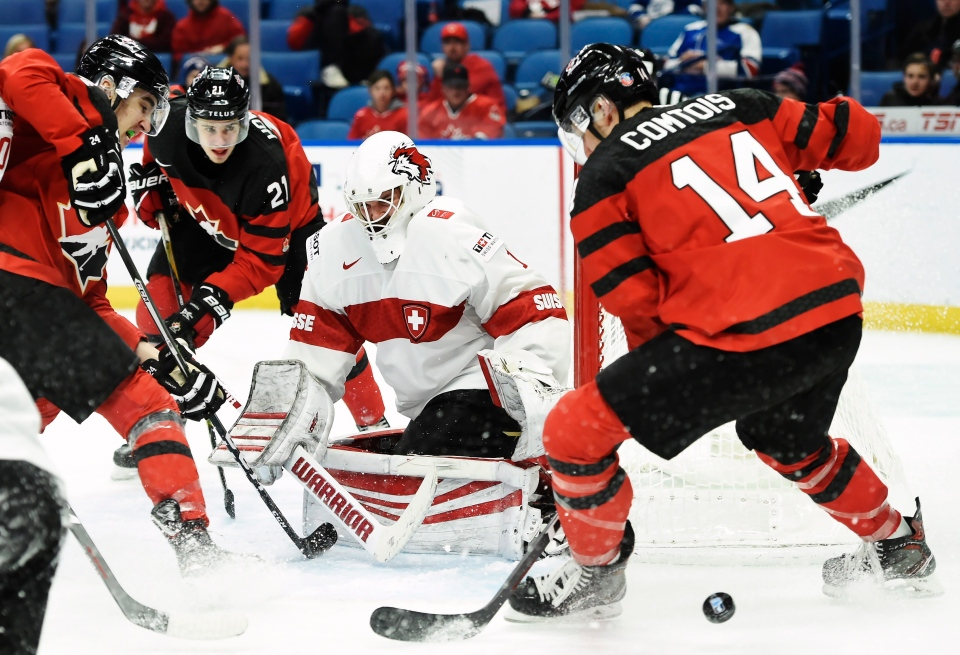 Switzerland's Matteo Ritz (1) makes a save as Canada's Alex Formenton, left to right, Brett Howden (21) and Maxime Comtois (14) look for a rebound during third period quarter-final IIHF World Junior Championships hockey action in Buffalo, N.Y. on Jan. 2, 2018. THE CANADIAN PRESS/Nathan Denette
