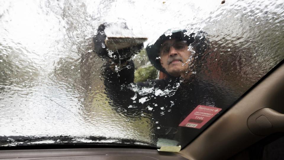 Omar Elkhalidi uses a wood shim to scrape ice off his windshield in Savannah, Ga., on Jan. 3, 2018. (Stephen B. Morton / AP)