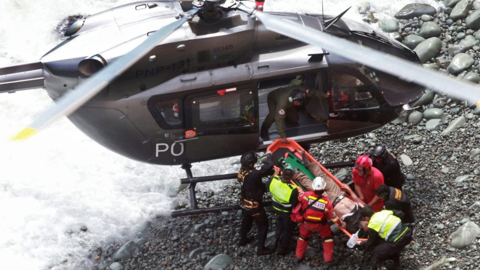 In this photo provided by the government news agency Andina, rescue workers load an injured man on a stretcher after he was retrieved from a bus that fell off a cliff after it was hit by a tractor-trailer rig, in Pasamayo, Peru, Tuesday, Jan. 2, 2018. (Vidal Tarky/Andina News Agency via AP)