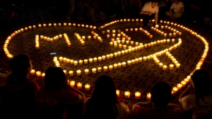 Relatives of Chinese passengers onboard Malaysia Airlines Flight 370 hold a candlelight vigil for their loved ones in Beijing pm April 8, 2014. (AP Photo/Andy Wong)