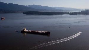 Crews on spill response boats work around the bulk carrier cargo ship Marathassa after a bunker fuel spill on Burrard Inlet in Vancouver, B.C., on Thursday April 9, 2015. (Darryl Dyck/THE CANADIAN PRESS)