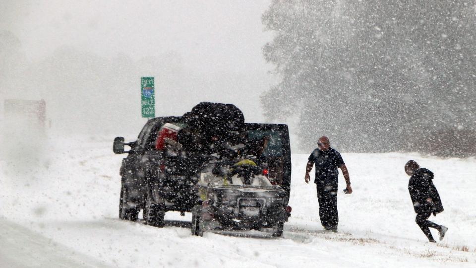 People attend to their vehicle on Interstate 26, near Savannah, Ga., Wednesday, Jan. 3, 2018. (Robert Ray/AP Photo)