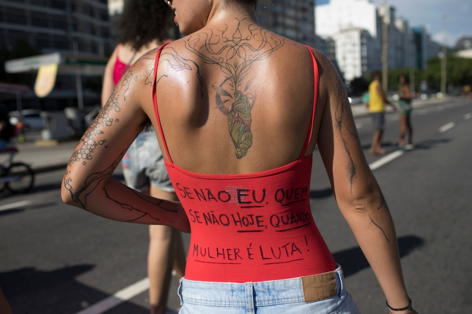"""In this Dec. 17, 2017 photo, a woman wears a shirt with text written in Portuguese on its back that reads """"If not me, who? If not today, when? To be a woman is to battle! """" during the annual """"Slut Walk"""" along Copacabana beac in Rio de Janeiro, Brazil. (Leo Correa/AP Photo)"""