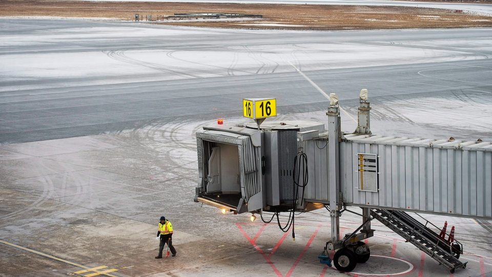 A worker walks on the tarmac at the Halifax Stanfield International Airport, where most flights have been cancelled, in Halifax on Thursday, Jan. 4, 2018.  (THE CANADIAN PRESS/Andrew Vaughan)