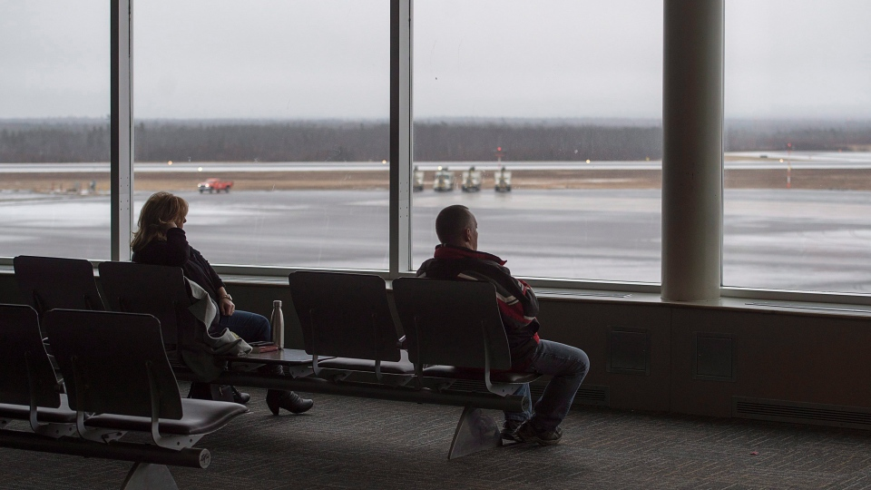 Passengers wait in a lounge at the Halifax Stanfield International Airport, where most arrivals and departures have been cancelled, in Halifax on Thursday, Jan. 4, 2018. (THE CANADIAN PRESS/Andrew Vaughan)