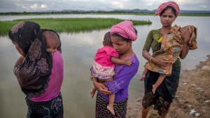 In this Oct. 18, 2017, file photo, Rohingya Muslim women who crossed over from Myanmar stand holding their sick children in Palong Khali, Bangladesh. (Dar Yasin/AP Photo)