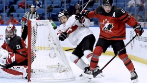 Canada's Dante Fabbro (8) vies for control of the puck with Switzerland's Philipp Kurashev (23) as Switzerland's Philip Wuthrich (30) looks on during second period quarter-final IIHF World Junior Championships hockey action in Buffalo, N.Y., on Tuesday, January 2, 2018. (Nathan Denette/THE CANADIAN PRESS)