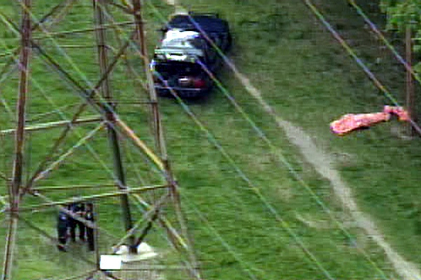 The body of a shooting victim is seen covered by a tarp on a hydro line right-of-way near Scarlett Road and Eileen Avenue on Monday, May 11, 2009.