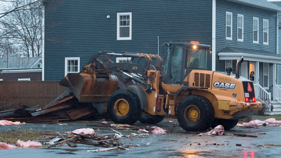 Workers clean up debris after a flat roof was torn from a small apartment building in Dartmouth, N.S. on Thursday, Jan. 4, 2018.  (THE CANADIAN PRESS/Andrew Vaughan)