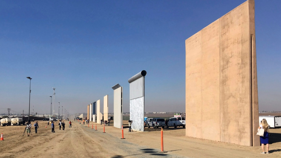 People look at prototypes of a border wall Thursday, Oct. 26, 2017, in San Diego. (AP Photo/Elliott Spagat)