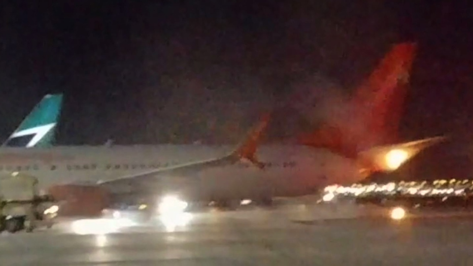 Flames are seen rising from the tail of a Sunwing plane in this video still obtained by CTV News.