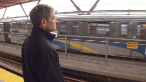 TransLink CEO Kevin Desmond watches as a SkyTrain pulls into a station.