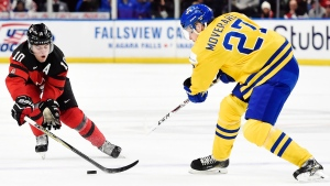 Canada defenceman Kale Clague (10) and Sweden defenceman Jacob Moverare (27) battle for the puck during third period gold medal game IIHF World Junior Championship hockey action in Buffalo, N.Y. on Friday, January 5, 2018. THE CANADIAN PRESS/Nathan Denette