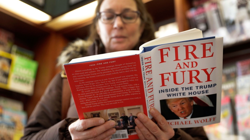 "Kathy Mallin, from Glenview, Ill., looks over a copy of the book ""Fire and Fury: Inside the Trump White House"" by Michael Wolff at Barbara's Books Store, Friday, Jan. 5, 2018, in Chicago. (AP Photo/Charles Rex Arbogast)"