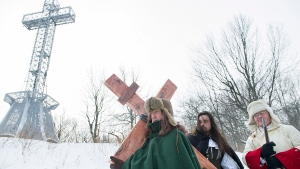 A man dressed as Paul de Chomedey de Maisonneuve, left, carries a crucifix to commemorate the 375th anniversary of the raising of the cross on Mount Royal in Montreal, on Jan. 6, 2018. THE CANADIAN PRESS/Graham Hughes