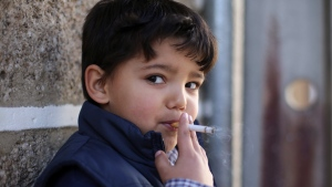 Fernando, 6-years-old, smokes a cigarette in the village of Vale de Salgueiro, northern Portugal, during the local Kings' Feast Saturday, Jan. 6, 2018. (AP Photo/Armando Franca)
