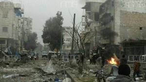 In this photo provided on Jan. 3, 2018 by the Syrian anti-government activist group, Edlib Media Center, EMC, which has been authenticated based on its contents and other AP reporting, shows members of the Syrian civil defense known as the White Helmets, gathering at a street which was attacked by Russian airstrikes, in Maarat al-Nuaman town, southern Idlib province, Syria. (Edlib Media Center)
