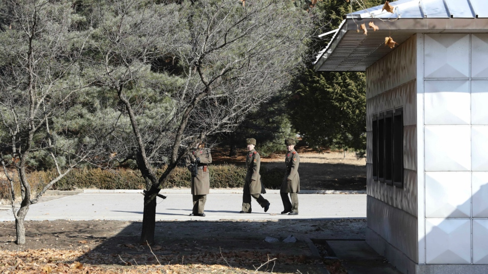 Three North Korean soldiers look at the South side at the spot where a North Korean soldier crossed the border on Nov. 13, at the Panmunjom in the Demilitarized Zone, South Korea on Nov. 27, 2017. (AP Photo/Lee Jin-man)