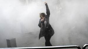 A university student attends a protest inside Tehran University while a smoke grenade is thrown by Iranian police, in Tehran, Iran on Dec. 30, 2017. (AP Photo)