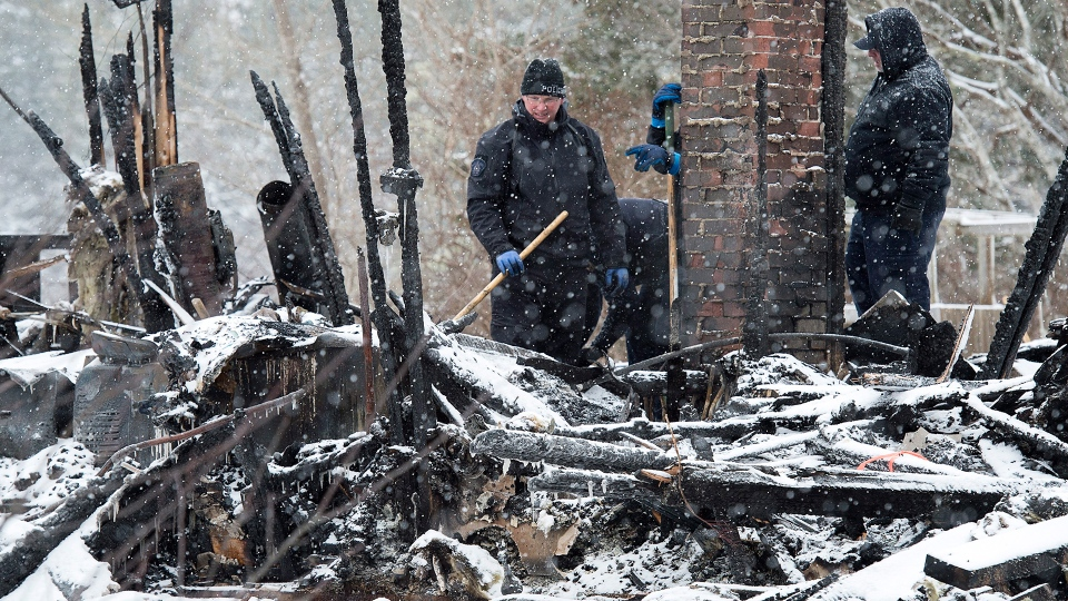 RCMP officers and a representative of the Medical Examiner's office search the scene of a house destroyed in a weekend fire in Pubnico Head, N.S. on Monday, Jan. 8, 2018. (Andrew Vaughan / THE CANADIAN PRESS)