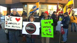 Protesters gathered outside select Tim Hortons locations this morning to speak out against some franchise owners who plan to hike benefit premiums and cut paid breaks following an increase in minimum wage.
