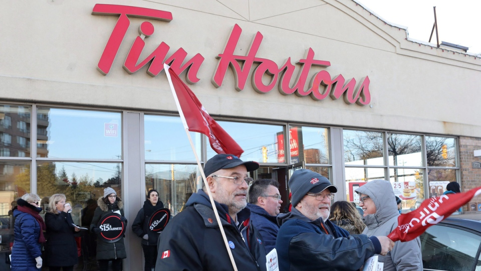 Members of Ontario Federation of Labour protest outside a Tim Hortons Franchise in Toronto on Jan. 10, 2018. (Chris Young / THE CANADIAN PRESS)