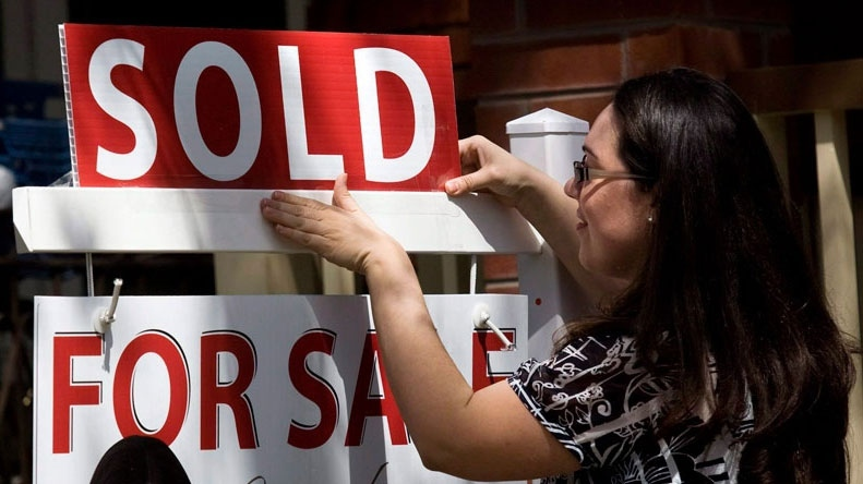 A real estate agent puts up a 'sold' sign in front of a house on Tuesday, April 20, 2010. (Darren Calabrese / THE CANADIAN PRESS)