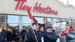 Members of Ontario Federation of Labour protest outside a Tim Hortons Franchise in Toronto on Wednesday January 10, 2018. Labour organizations across Ontario are holding rallies today to protest the actions some Tim Hortons franchises have taken in response to an increase in the province's minimum wage. THE CANADIAN PRESS/Chris Young