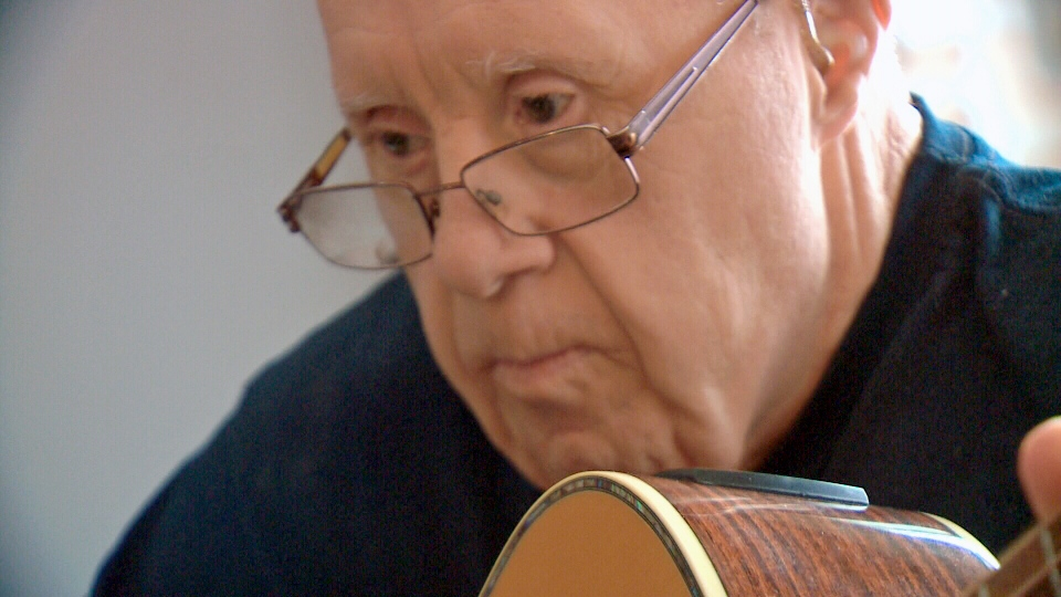 Jerry Kryzanowski plays guitar at a family member's home in Saskatoon.
